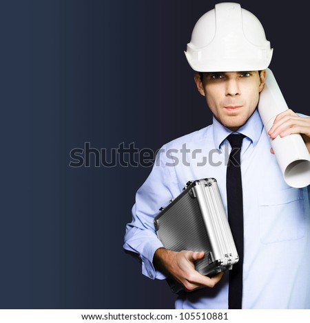 Driven and determined young male engineer in building hardhat carrying briefcase and blueprint on dark blue copyspace background - stock photo
