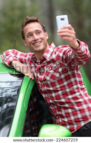 Driver by car taking selfie photo with smartphone after driving in new green car. Happy man taking picture with smartphone camera during travel road trip. Young Caucasian male model in his 20s. - stock photo