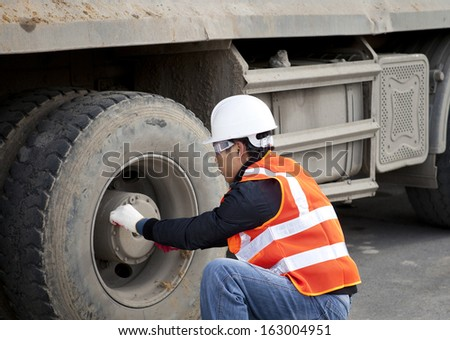 Driver construction worker checking tyre truck - stock photo