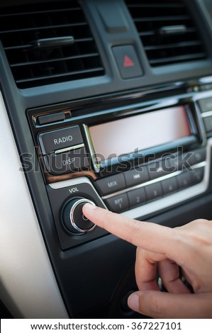 Driver finger pushing button of car audio stereo player. - stock photo