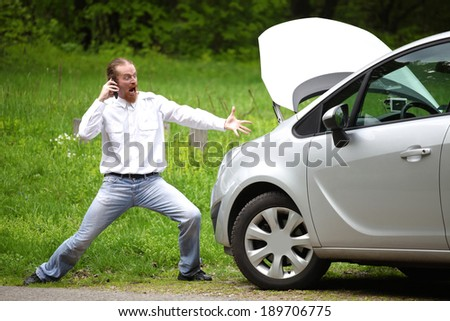 Driver furious with mobile phone a broken car by the road  - stock photo