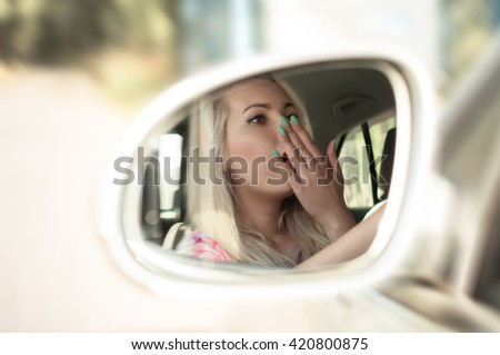 Driver girl yawns while driving a car in the mirror