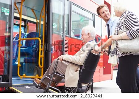 Driver Helping Senior Couple Board Bus Via Wheelchair Ramp - stock photo