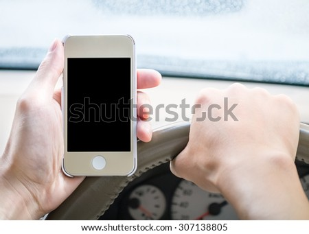 Driver holding blank screen smartphone in the car while driving in slightly rain - stock photo