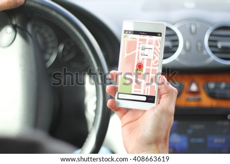 driver holding smartphone with gps map app interface. All screen graphics are made up. - stock photo