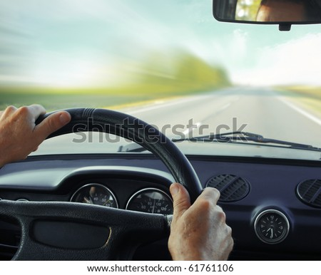 Driver in car holding steering wheel. Blurred road and sky - stock photo