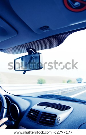 Driver in car holding steering wheel. Blurred road and sky-3 - stock photo