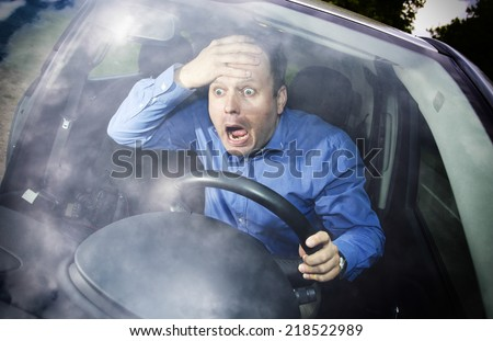 Driver in horror after car accident holding hand on his head - stock photo