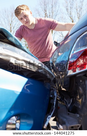 Driver Inspecting Damage After Traffic Accident - stock photo