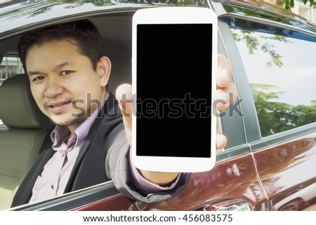 Driver is showing mobile phone with black blank screen while sitting in a car. Photo is focused at mobile screen and includes CLIPPING PATH for mobile screen.