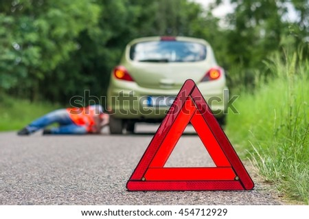 Driver lying under the broken car and warning triangle
