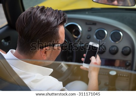 Driver man using smartphone in car