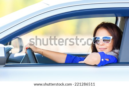 Driver of car girl in sunglasses