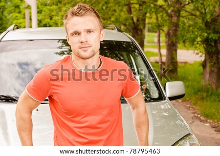 Driver of car stands about cowl against summer nature.
