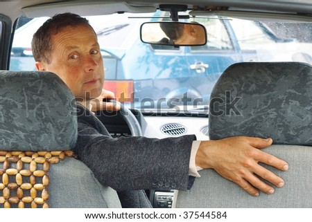 Driver of the car looking back - stock photo