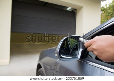 driver opens the garage with remote control from the comfort of a car - stock photo