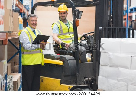 Driver operating forklift machine next to his manager in warehouse - stock photo