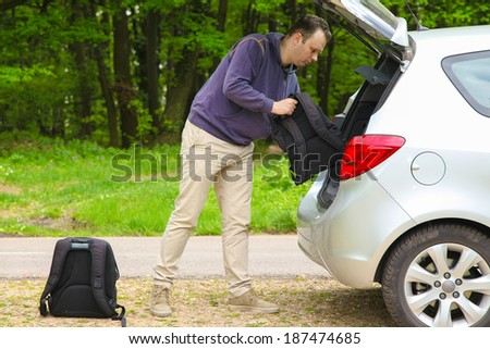 Driver packs backpacks in the trunk of his car before travel - stock photo