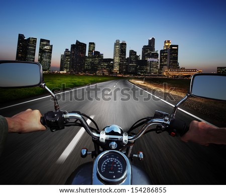 Driver riding motorcycle on an asphalt road at night towards big city - stock photo
