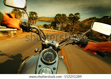 Driver riding motorcycle on an asphalt road in a tropics - stock photo