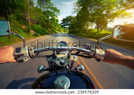 Driver riding motorcycle on an asphalt road through forest - stock photo