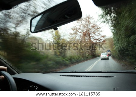 Driver's hand on a steering wheel of a car and road - stock photo