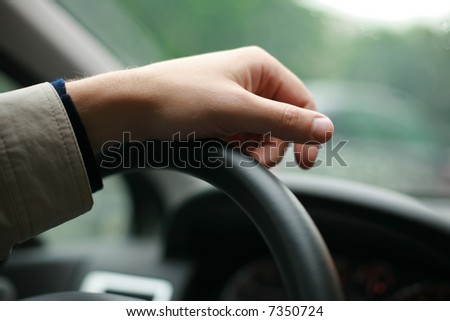 Driver's hand on steering wheel. Shallow DOF.