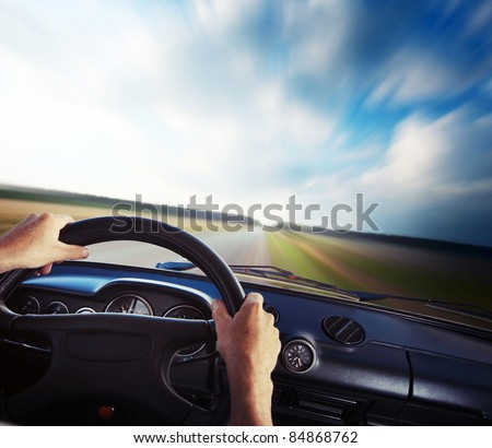 Driver's hands on a steering wheel and blurred road - stock photo