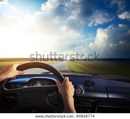 Driver's hands on a steering wheel and motion blurred road - stock photo