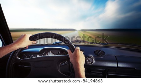 Driver's hands on a steering wheel and motion blurred road and sky - stock photo