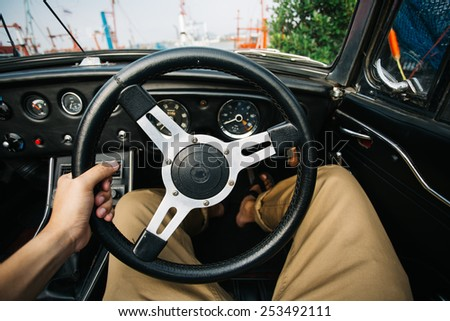 Driver's hands on a steering wheel of a car. - stock photo