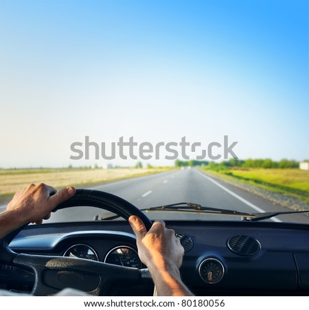 Driver's hands on a steering wheel of a retro car during riding on an empty asphalt road - stock photo