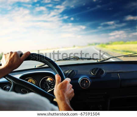 Driver's hands on steering wheel - stock photo