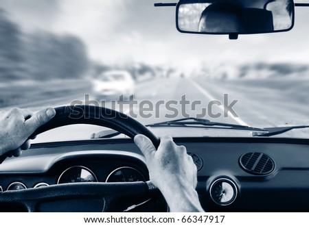 Driver's hands on steering wheel inside of a car - stock photo
