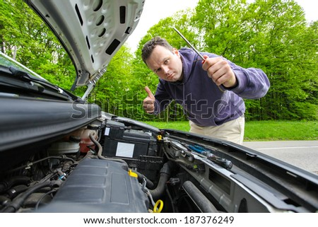 Driver showing thumb up after fixing his car - stock photo
