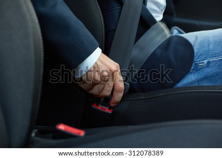 Driver sits in the car and fastens his seat belt - stock photo
