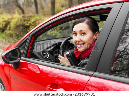 Driver smiling girl in a red car - stock photo