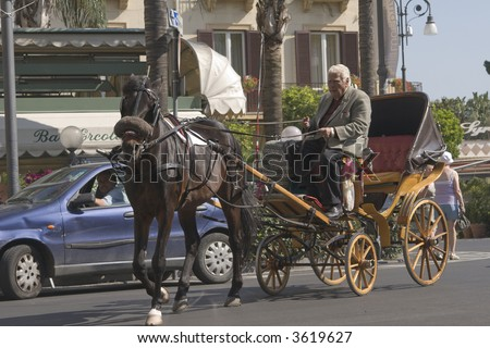 Driver steers a horse-drawn carriage among traffic in Sorrento, Italy.