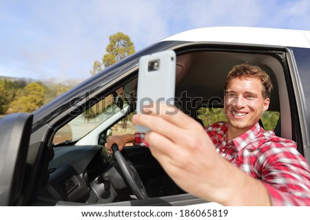 Driver taking photo with camera smartphone driving in car. Happy man taking picture with smart phone camera out window of car during travel road trip. Young Caucasian male model in his 20s. - stock photo