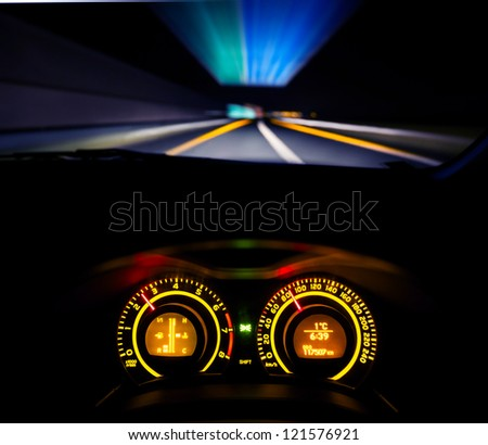 Driver view at speeding car  dashboard and motorway  at night - stock photo