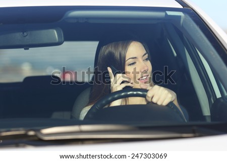Driver woman driving a car distracted on the phone and looking at side - stock photo