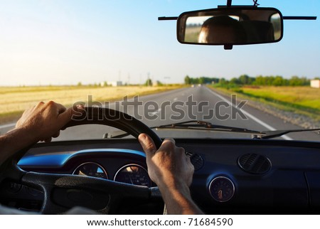 Drivers's hands on a steering wheel of a car - stock photo