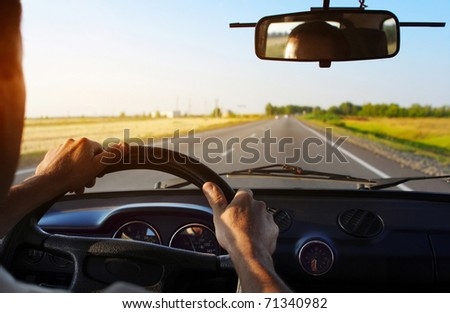 Drivers's hands on stearing wheel of a car - stock photo