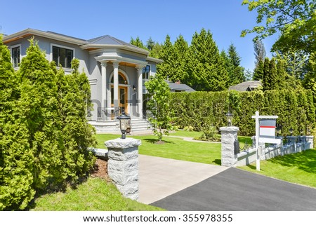Driveway and big front yard of brand new family house in suburban of Vancouver. Home for sale. Stylish residential house with wooden door and big front yard.  - stock photo