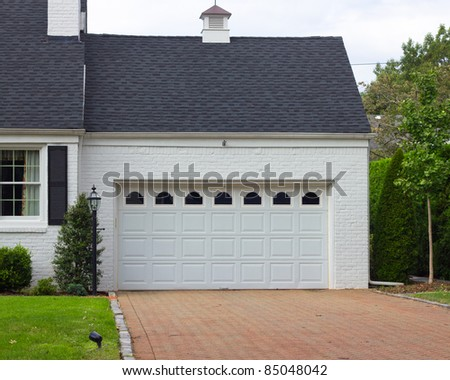 Driveway and garage in a typical American suburban neighborhood - stock photo
