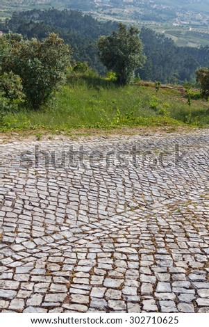 Driveway made out of old cobblestone in a rural area. Up on a hill, a rural valley is below in the background. - stock photo