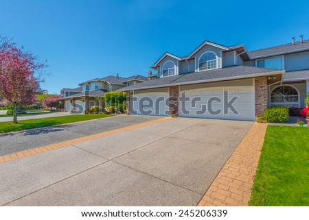 Driveway to garage. Nice and great neighborhood. Some homes on the empty street in the suburb of North America. Canada.