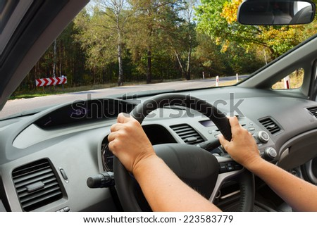 driving a car at country road, view  inside out, making a turn - stock photo