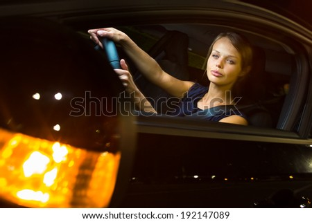 Driving a car at night - pretty, young woman driving her modern car at night, in a city (shallow DOF; color toned image) - stock photo