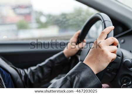 Driving a car, hands on steering wheel